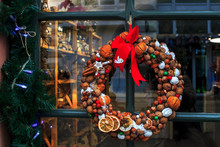 Christmas Wreath From Nuts, Tangerines, Cinnamon And Red Bow On Door