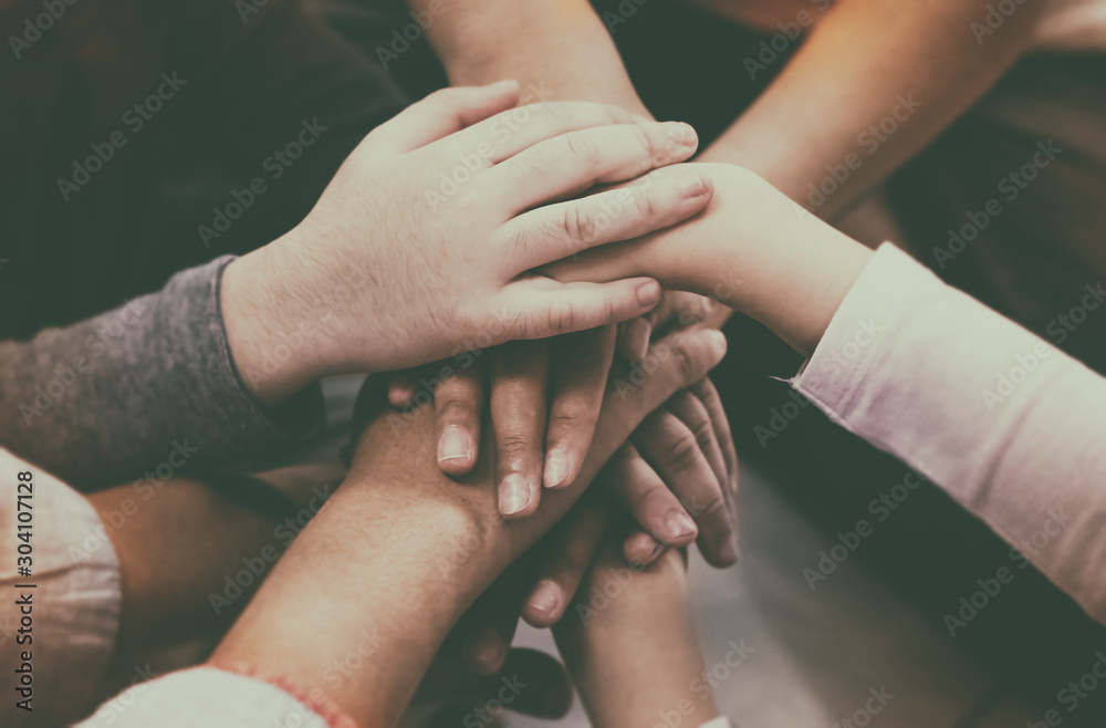 Fototapeta The abstract art design background of adult and children hands stacked together,collaborator,union,joining teamwork concepts,vintage and art tone,classic old film style,blurry light around