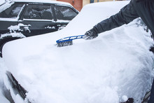 Man Cleaning Car From Snow And...
