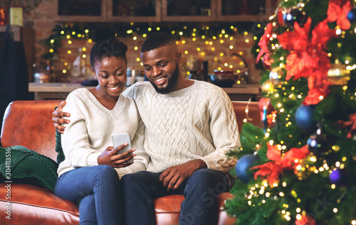 Leinwand Poster  Smiling black couple using smartphone at home reading Christmas wishes