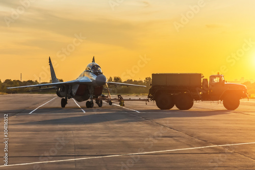 Obraz Military fighter is being pushed to a parking lot by a military vehicle at an air base in the evening at sunset. - fototapety do salonu