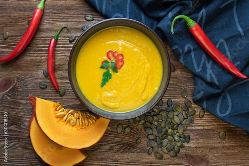 Fototapeta Zupa z dyni na ciemnym drewnianym tle. obraz