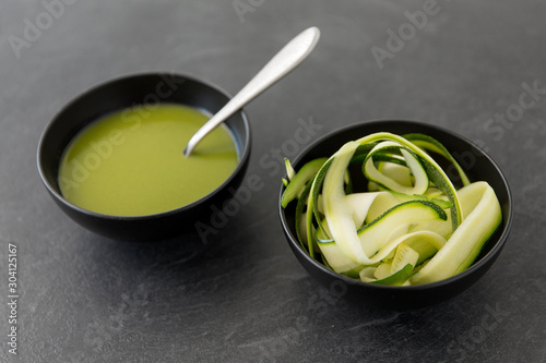 vegetable, food and culinary concept - close up of peeled or sliced zucchini and cream soup in ceramic bowl on slate stone background