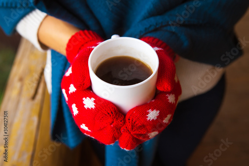 Foto auf Leinwand Kaffee girl in red mittens holding a cup of coffee