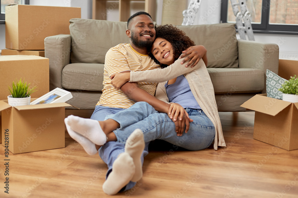 Fototapeta moving, repair and real estate concept - happy african american couple with cardboard boxes hugging at new home