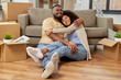 moving, repair and real estate concept - happy african american couple with cardboard boxes hugging at new home