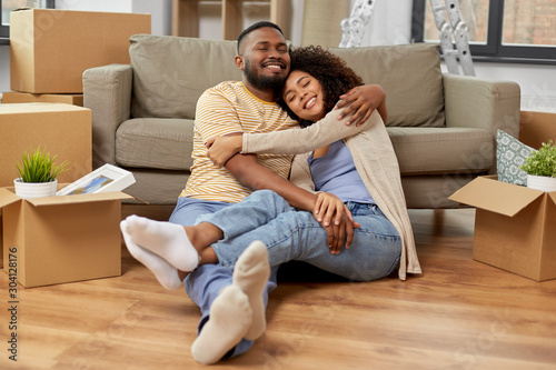 Fotobehang Vrouw gezicht moving, repair and real estate concept - happy african american couple with cardboard boxes hugging at new home