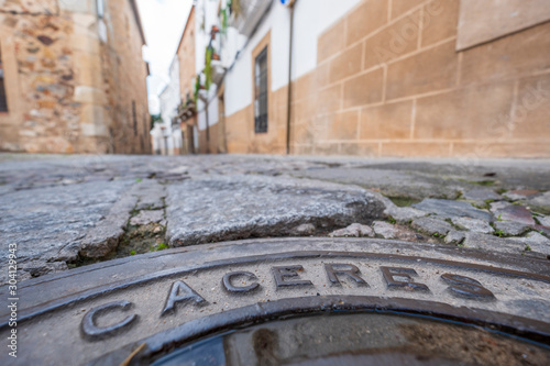 manhole cover in the streets with inscription caceres in the old eponymous historic capital of the province of caceres, extremadura, spain