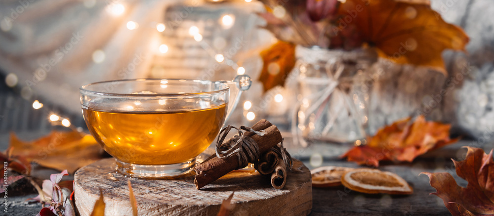 Fototapeta Cozy autumn or winter at home. A cup of tea, autumn casts a book a garland on a wooden table near a bed with warm plaids. Lifestyle autumn hygge lagom?concept of a holiday and autumn weekend.Banner