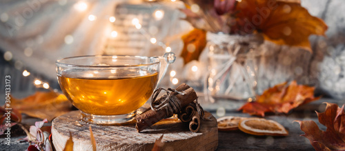 Tuinposter Thee Cozy autumn or winter at home. A cup of tea, autumn casts a book a garland on a wooden table near a bed with warm plaids. Lifestyle autumn hygge lagom?concept of a holiday and autumn weekend.Banner