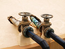Close-up Of Old Water Valve And Industrial Pipes, Old Rust-proof Water Control Equipment With Plastic Pipes On The Cement Floor Background