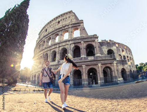 Obraz Young happy couple of tourist walking holding hands at Colosseum. Come with me. Rome, Italy - fototapety do salonu