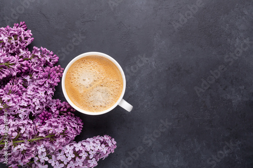 Foto op Canvas Lilac Cup of morning coffee with spring lilac flowers branches blossoming on black stone background Top view