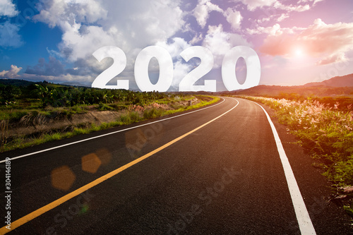 Foto auf Leinwand Schokobraun The word 2020 behind the tree of empty asphalt road at golden sunset and beautiful blue sky. Concept for vision year 2020.