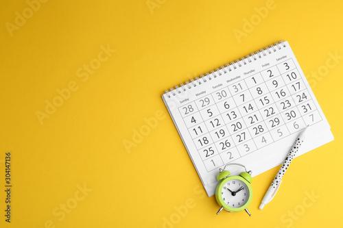 Tela Calendar, pen and alarm clock on yellow background, flat lay