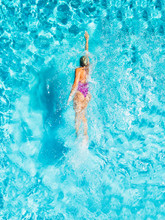 A Woman Is Swimming In A Pool, Seen From Above. She Looks Tiny In The Huge Pool.
