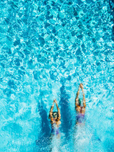 Two Women Is Swimming In A Pool, Seen From Above. She Looks Tiny In The Huge Pool.