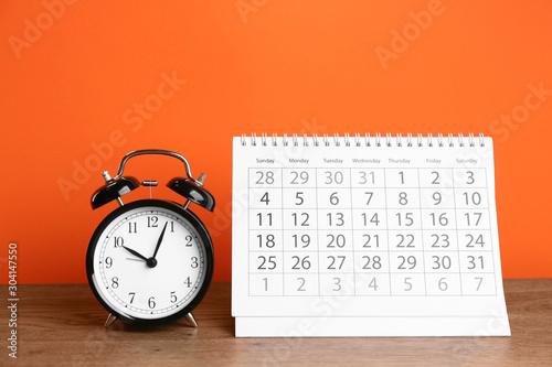 Fotografia Calendar and alarm clock on wooden table against orange background
