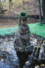 In The Middle Of The Lake Is A Carved Wooden Statue Of A Mermaid Or A Water Statue In A Cylinder.