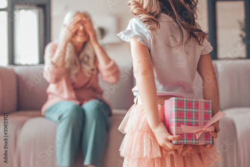 Obraz girl holding present box in the hands behind her back and making surprise for grandmother sitting on the couch - fototapety do salonu