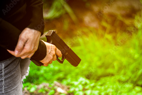 Fotomural  woman holding a gun in hand. - violence and crime concept.