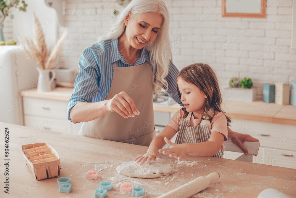 Fototapeta grandmother sprinkling flour on the dough for cookies while granddaughter playing with dough
