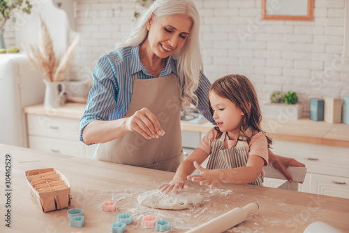 Obraz grandmother sprinkling flour on the dough for cookies while granddaughter playing with dough - fototapety do salonu