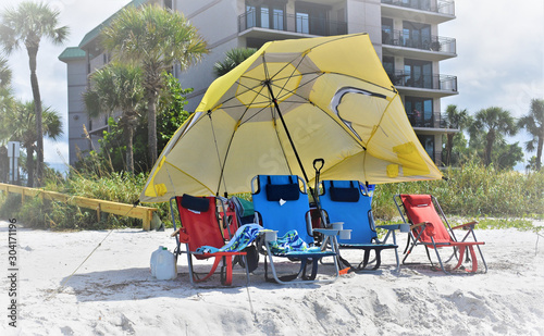Vászonkép  Yellow Beach Umbrella and colorful beach chairs in a Florida message convery the