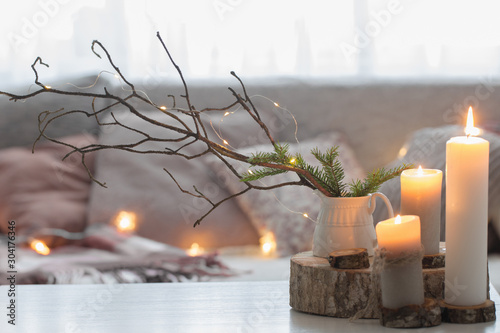 Stampa su Tela  Composition of candles on  white table against the background of  sofa with plaids and pillows