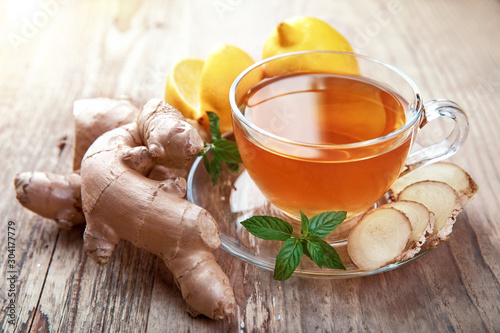 Tuinposter Thee Ginger tea with lemon and mint in glass cup at old wooden board in rustic style.