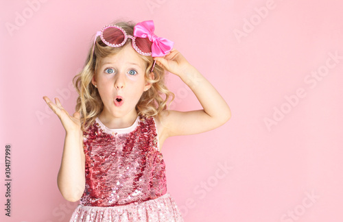 Portrait of a shocked girl wearing pink shiny dress and glasses Fototapet