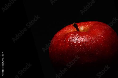 apetyczne-czerwone-jablko-pokryte-kroplami-wody-na-czarnym-tle
