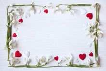 White Wooden Background With Spring Snowdrops And Red And White Hearts.