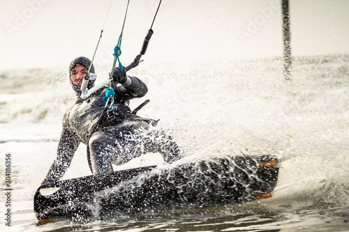 Kitesurfer riding his kiteboard along the coast of the Germany Sea in St. Peter Ording.