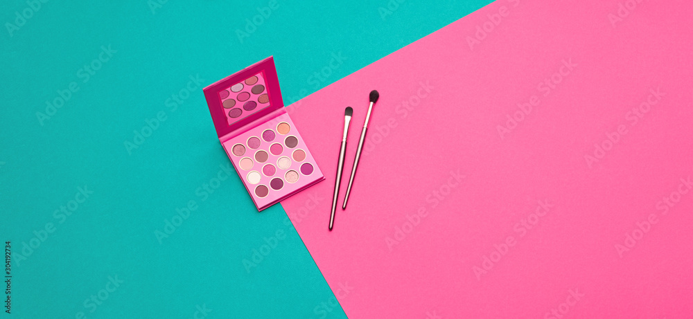 Fototapeta Cosmetic makeup accessories pink flat lay. Fashion creative minimal Set. Trendy eye shadow palette, brushes. Art colorful geometry pink Style. Beauty cosmetic make up tools, fashionable banner