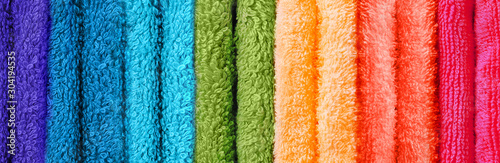 Row of coloured towels folded up vertical image Fototapete
