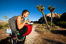 A Woman Refers To A Climbing Guide Book Near Turtle Rock In The Hidden Valley Picnic Area At Joshua Tree National Park.