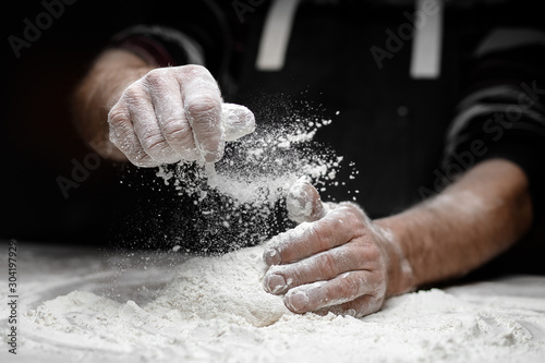 White flour flies in air on black background, pastry chef claps hands and prepar Canvas Print