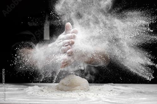 Obraz na płótnie Chef man clap hand and white flour dust on black background