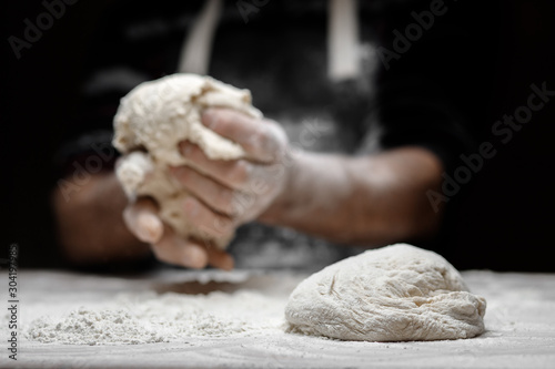 Tela Hands of male baker preparing yeast dough with white flour dust on black backgro