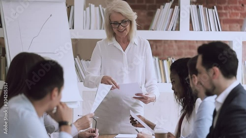 Fotografía  Older female boss presenting work plan give papers to employees
