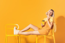 Fashionable Young Woman With Coffee Sitting On Chair Near Color Wall