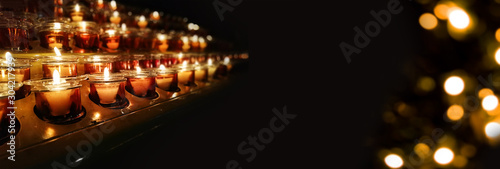 Candles in a church, cathedral or temple, in yellow transparent candlesticks Fototapete