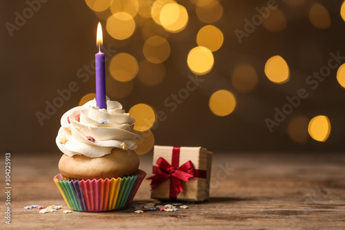 Birthday cupcake with candle and gift box on wooden table against blurred lights. Space for text