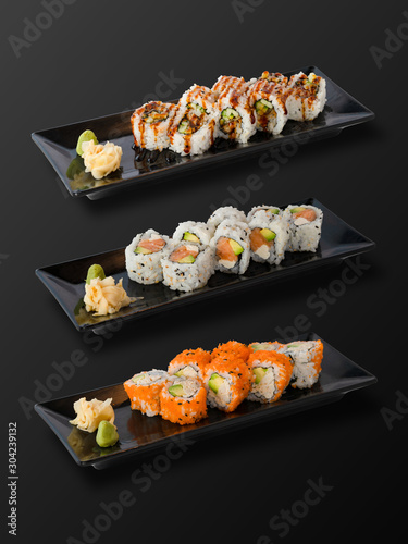 Fototapeta Isolated on black background of Set of Sushi Rolls in black plate. Clipping Path Included. obraz