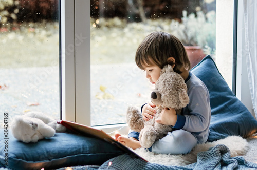 Cute little boy reading book hugging his teddy bear toy sitting cozy on pillows and knitted blanket  at window Tablou Canvas