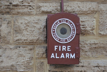Old Fire Alarm On Brick Wall
