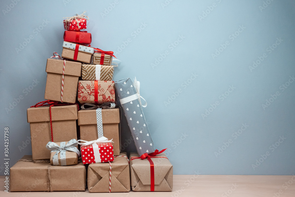 Fototapeta pile of wrapped christmas gifts on blue background