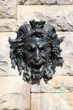 Occult Horned, Goat Man Face Statue Carving Mounted On A Tan, Cement Brick Wall Outdoors