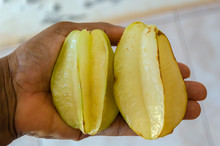 Two Starfruit In The Palm Of A Hand